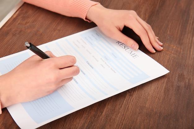 テーブルの上の履歴書フォームに記入する女性。就職の面接のコンセプト