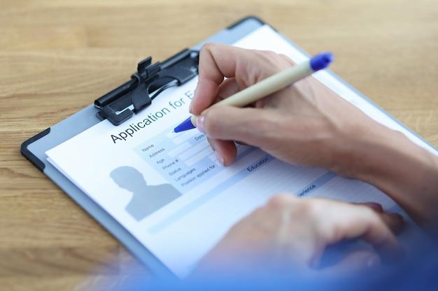 실업과 싸우는 볼펜 클로즈업으로 고용 문서를 작성하는 여자