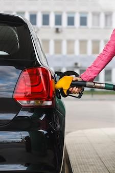 Woman filling up the car at petrol station