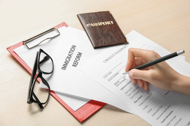 테이블에서 긴급 여권 신청서를 작성하는 여자. 이민 및 시민권