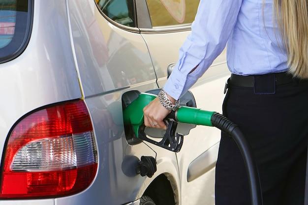女性はガソリンスタンドのクローズアップで彼女の車にガソリンを塗りつぶします。駅で燃料ポンプを持つ女性の手。