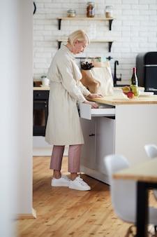 台所の引き出しに道具を見つける女性