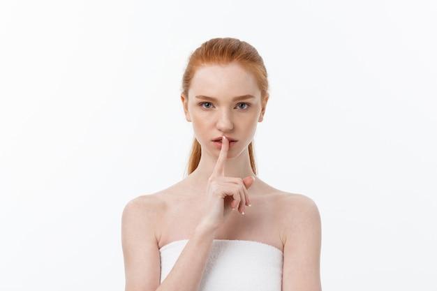 口の上の女性の指、静かな唇の沈黙のサイン