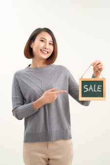 Woman finger point to chalkboard and showing sale word