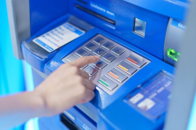 Женщина палец, который нажимает кнопку банкомата