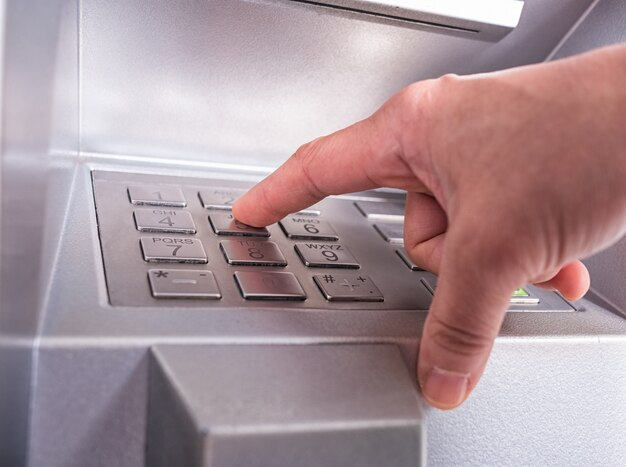 Woman finger pressing the enter key button on the keyboard of a automatic teller machine