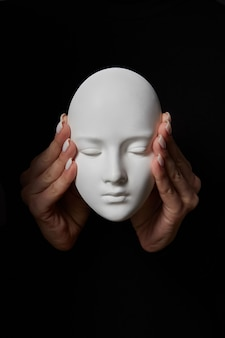 Woman fingers close ears of gypsum mask face on a black wall. hear no evil. concept three wise monkeys. place for text.