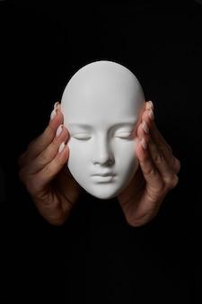 女性の指が黒い壁の石膏マスクの顔の耳を閉じます。悪を聞いてはいけません。三猿のコンセプト。テキストの場所。