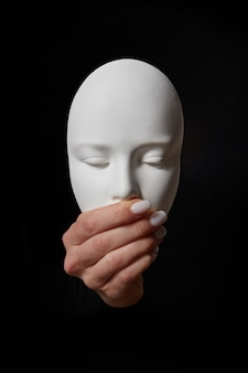 Woman fingers close mouth of gypsum mask face on a black wall, copy space. speak no evil. concept three wise monkeys