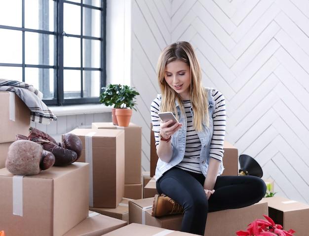 女性は貨物パッケージを使い終え、配送のために宅配便業者に電話をかけています