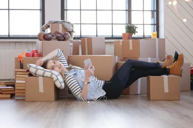 Женщина закончила с грузовыми пакетами и лежит на полу
