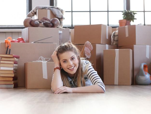 女性は貨物パッケージで終了し、床に横たわっています