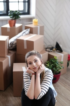 여자는화물 패키지를 완료하고 바닥의 상자 옆에 앉아있다