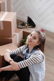 화물 패키지를 완료하고 상자 옆에 앉아있는 여자