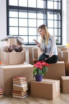 Woman finished with cargo packages and is calling a courrier for shipping