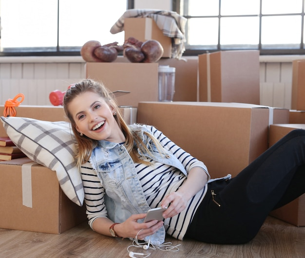 Woman finished with cargo packages and is checking her phone and laughing
