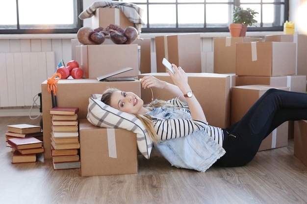 Woman finished with cargo packages and is checking her phone