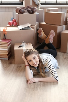 Woman finished with cargo packages and is lying on the floor