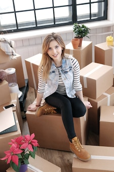 Woman finished with cargo packages and is sitting on the boxes