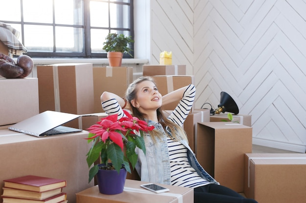 Woman finished with cargo packages and is sitting on the floor in a satisfied manner