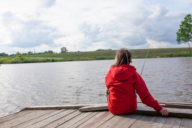 여성 어부는 뷰어에 등을 대고 앉아 손에 낚싯대를 들고 있습니다. 물고기를 잡는 여성 낚시하는 소녀