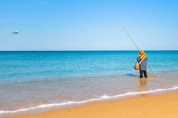 열 대 해변에서 해안 하늘 드롭 비행기 화창한 맑은 아침 근처 물에 서있는 여자 낚시