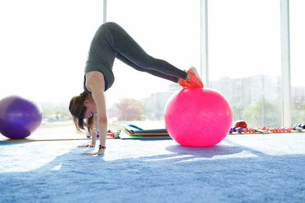 Woman fitness. beautiful caucasian senior woman doing exercise with ball in gym