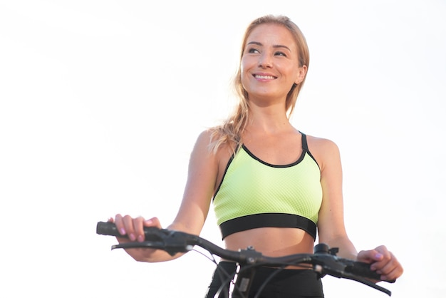 Woman in fitness clothes having a bike low view