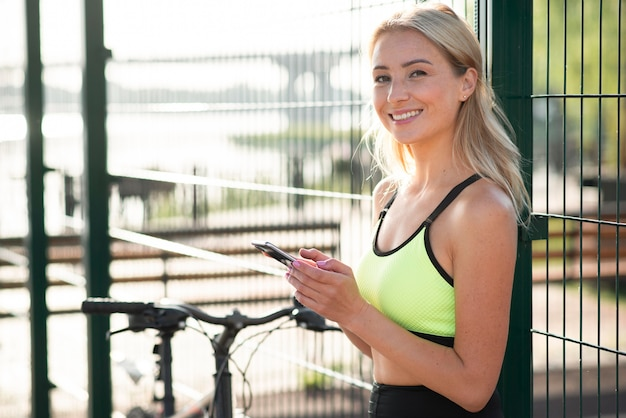 Woman in fitness clothes using her  mobile phone