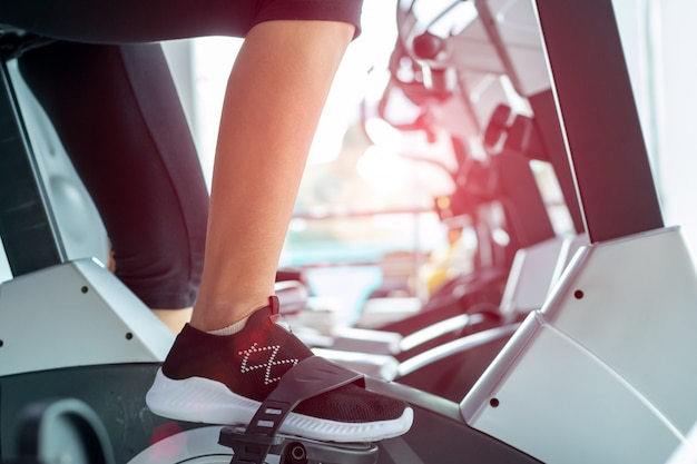 Woman on fitness exercise bike at indoor.