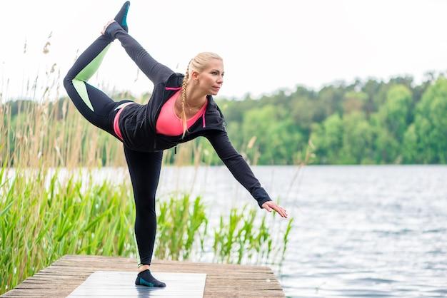 Женщина фитнес растяжения на пристани на озере