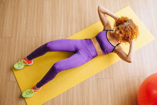 Woman fitness trainer lying on mat