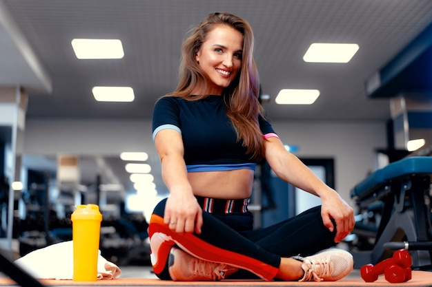 Woman fitness trainer portrait on a gym background
