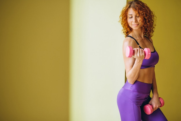 Woman fitness trainer with dumbbells