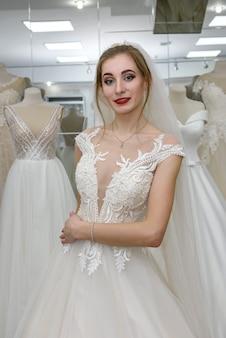 ショップでウェディングドレスとベールに合う女性