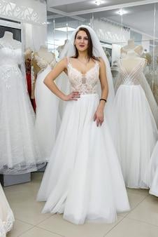 Женщина примеряет свадебное платье и вуаль в магазине