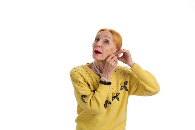 白い背景で隔離のイヤリングシニア女性を修正する女性