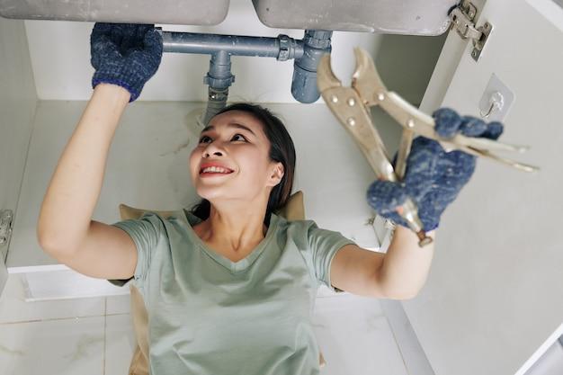 Женщина, ремонтирующая протекающую трубу