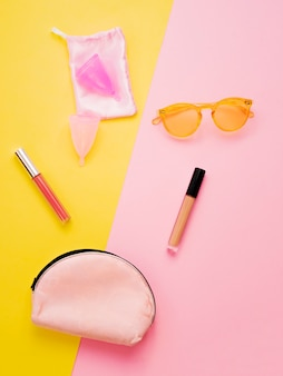 Woman flat lay with menstrual cup, lipstick, sunglasses and beauty case on pink and yellow background.