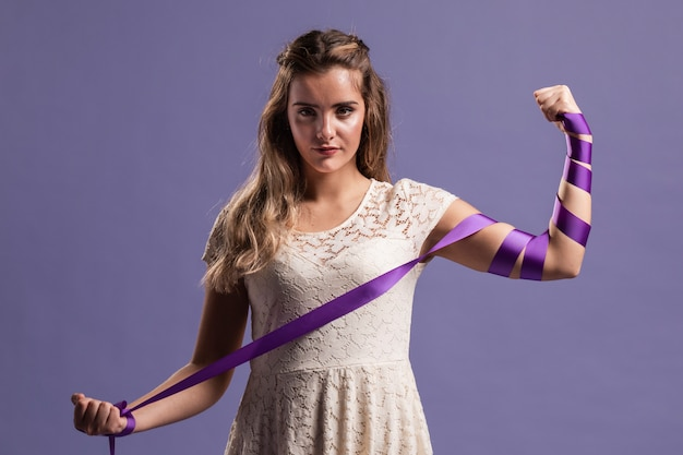 Woman flexing her arm with ribbon as a sign of strenght