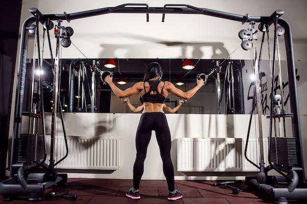 체육관에서 케이블 기계에 근육을 flexing 여자