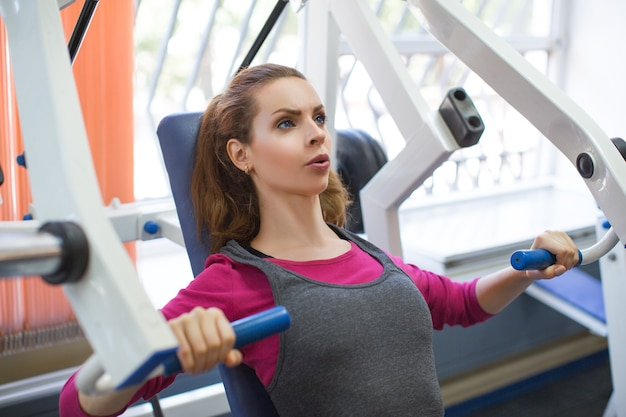 ジムの着席チェストプレス機で筋肉を曲げる女性。健康的なライフスタイルのコンセプト。