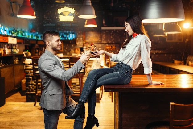Woman flirting with man, love couple at bar counter. lovers leisures in pub, husband and wife relaxing together in nightclub
