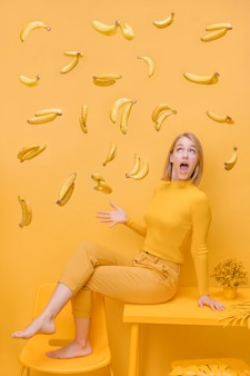 Woman and floating bananas in a yellow scene
