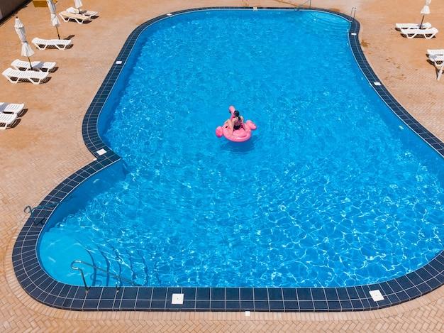 수영장 플라밍고에 떠 있는 여자 호텔 수영장에서 부유물