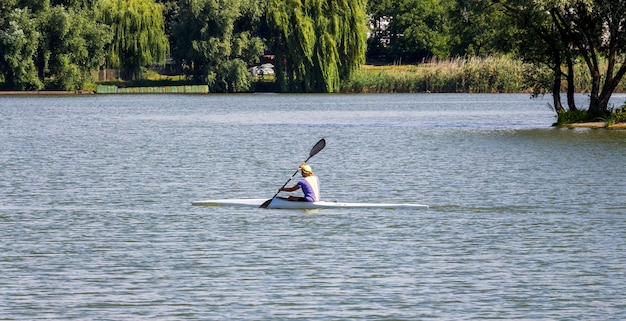 Woman floats on kayaking  on the river along the shore with trees_