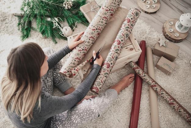 女性のフローリングと包装紙の切断