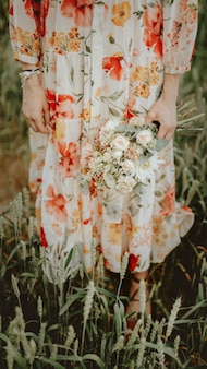 Woman in a floral dress holding a flower bouquet