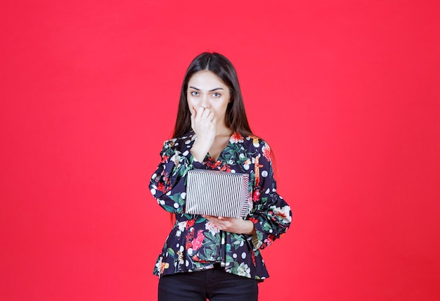 Woman in floral shirt holding a silver gift box and looks thoughtful.