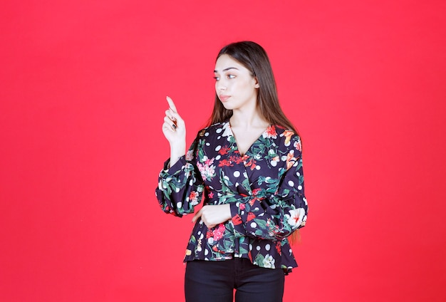 Woman in floral shirt standing on red wall and showing upside.
